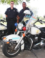 Two JPSO Motorcycle Escorts standing next to their motorcycles.